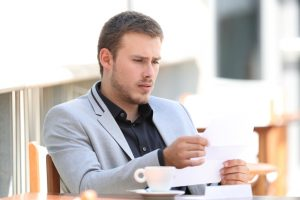 Worried man looking at wrong amount of debt collection